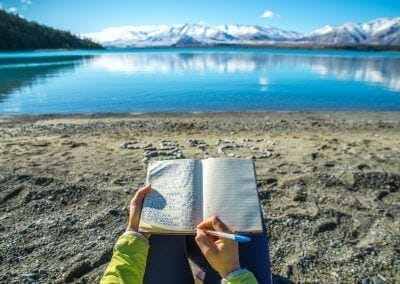 Happy Young woman writing a diary in nature